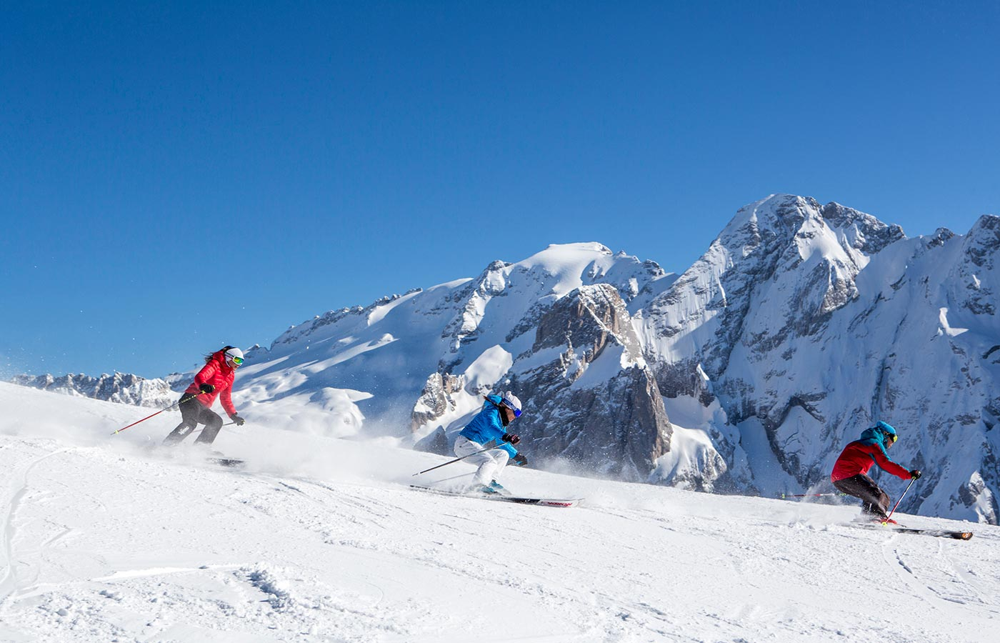 Three skiers start the descent from the mountain