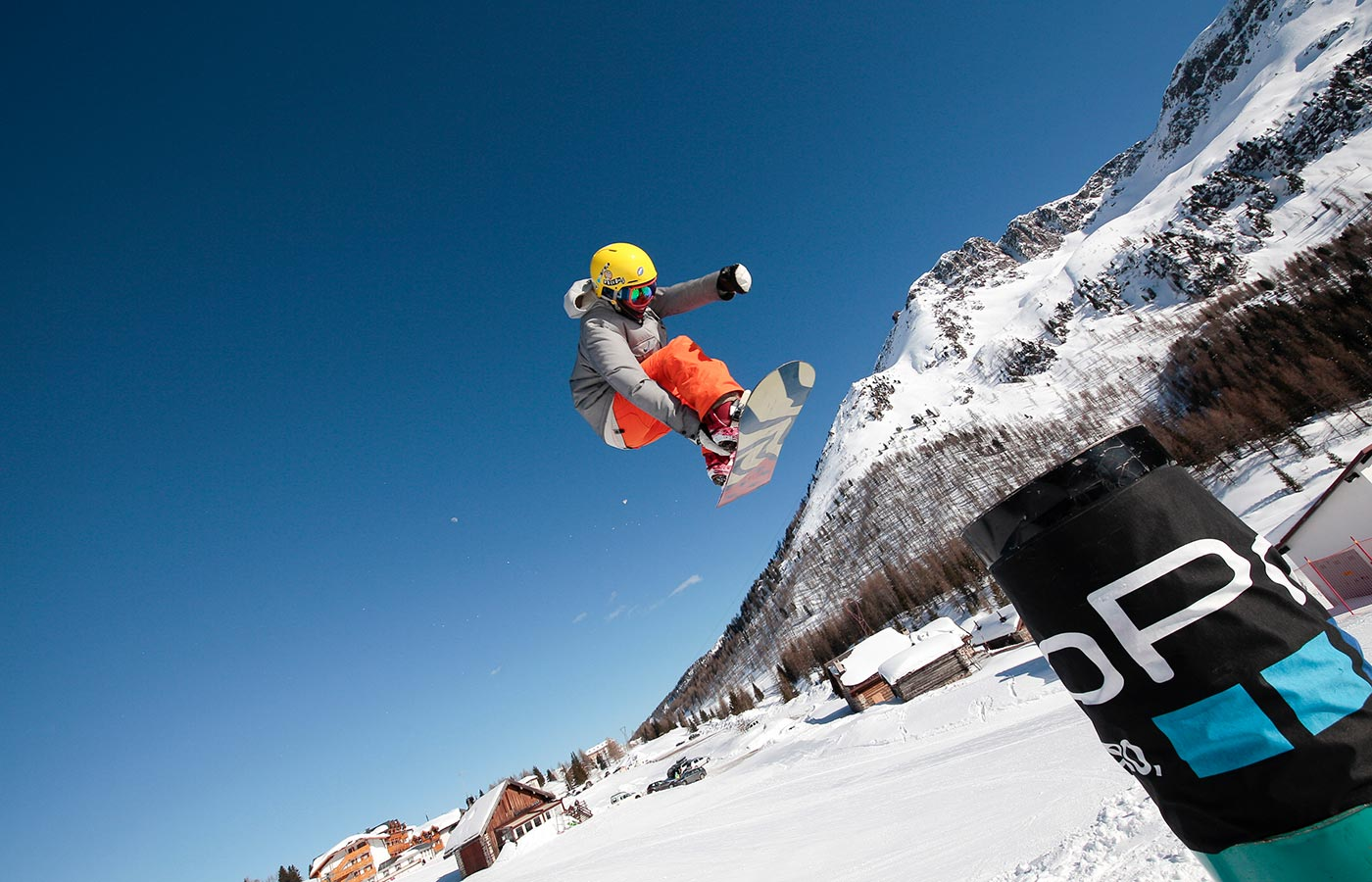 Snowboarder performs jumps and performances in Val di Fassa